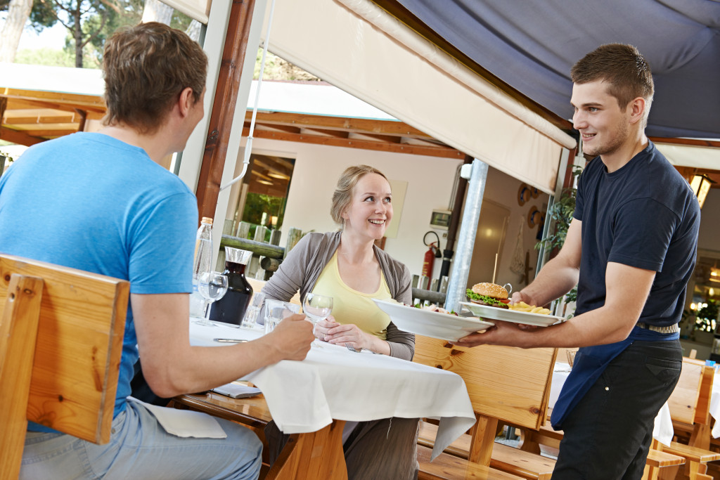 waiter serving young people in restaurant