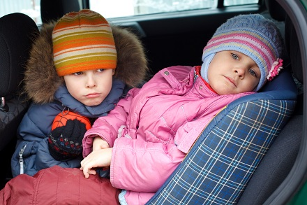 The sad boy with the little girl, in winter clothes in the car.