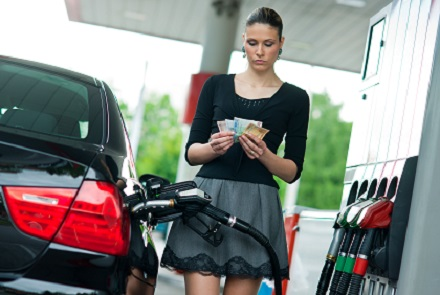 woman counting money on gas station