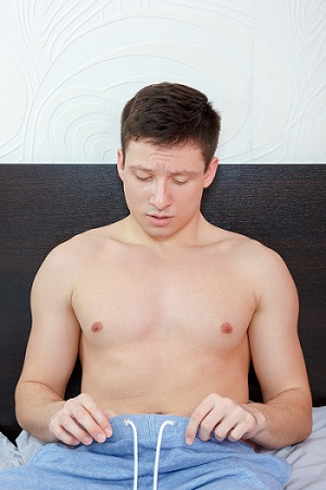 Young man in bed having problems with potency