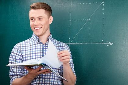 Vivacious student standing near blackboard.