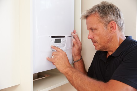Middle aged boiler technician servicing a domestic boiler