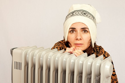 Young woman freezing near the heater