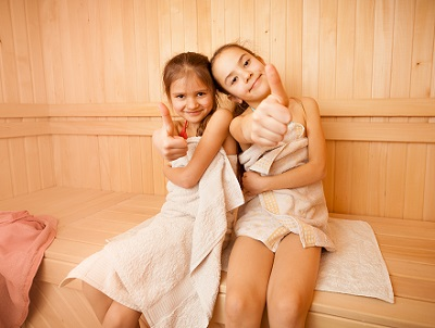 Two happy little girls in sauna showing thumbs up