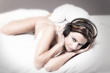 Gorgeous woman with white lingerie and headphones in the bed